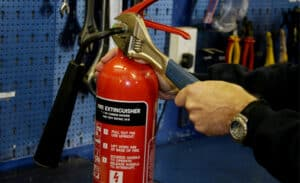 man servicing fire extinguisher in the workshop