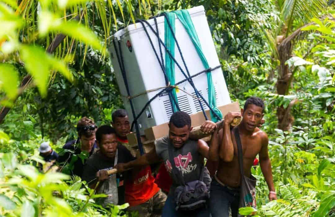 YWAM PNG Islanders carrying fridge in jungle