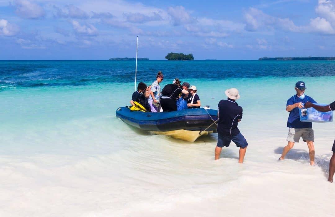 YWAM boat crew holding zodiac on beach