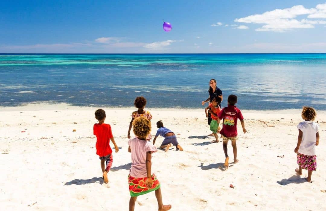 YWAM girls playing with village children on beach