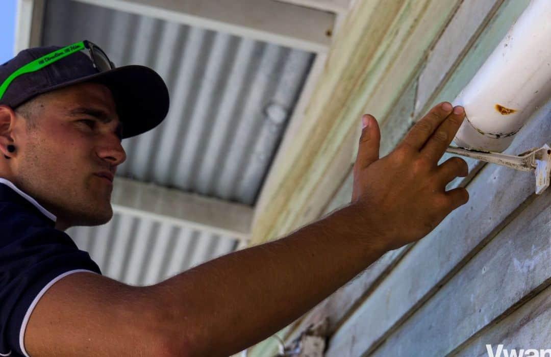 YWAM man fixing rain water pipe