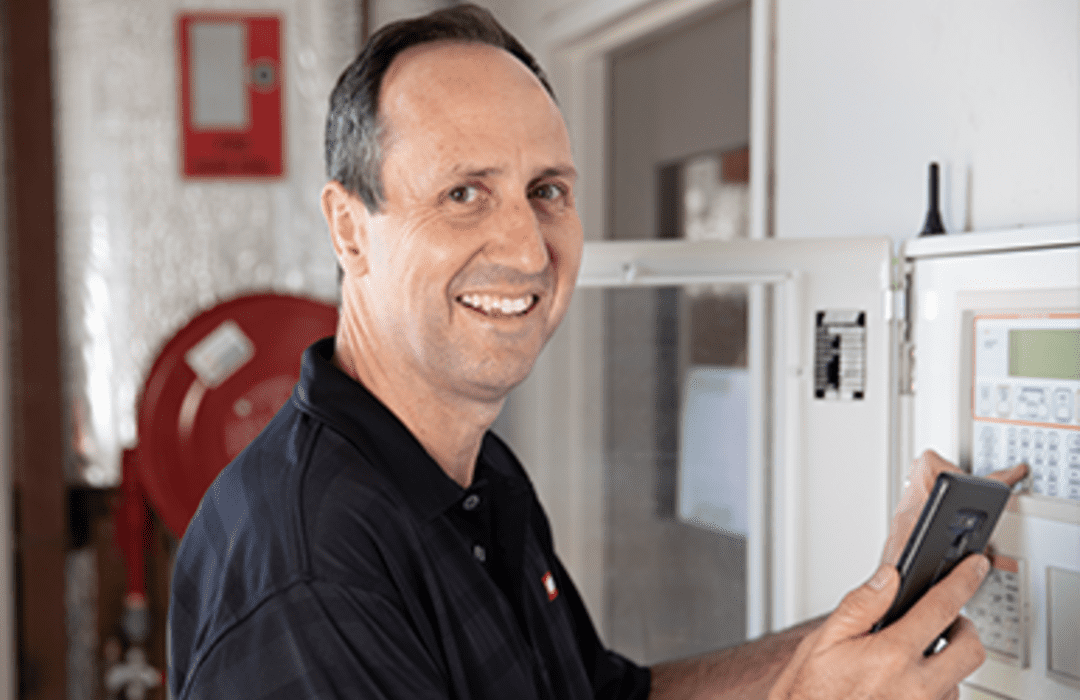 man checking fire alarm panel with FireMate software